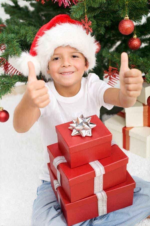 Garçon heureux avec un bon nombre de cadeaux de Noël images stock