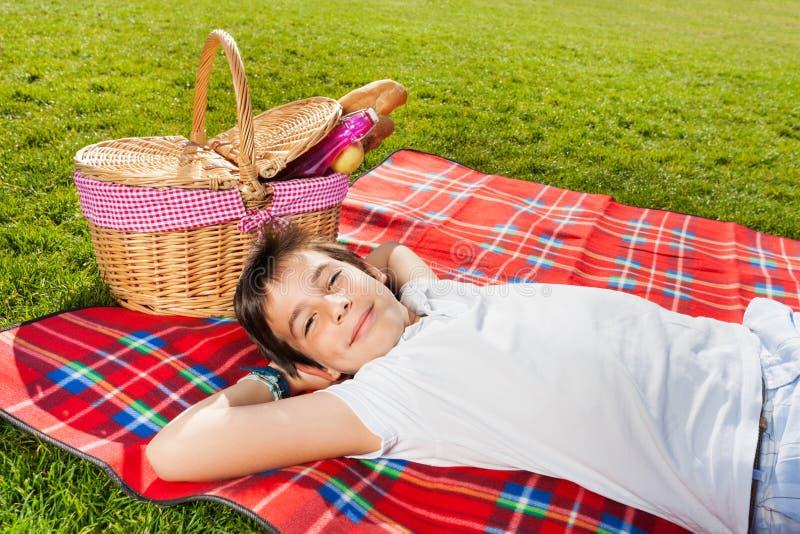 Garçon heureux détendant sur le pique-nique à côté du panier images stock