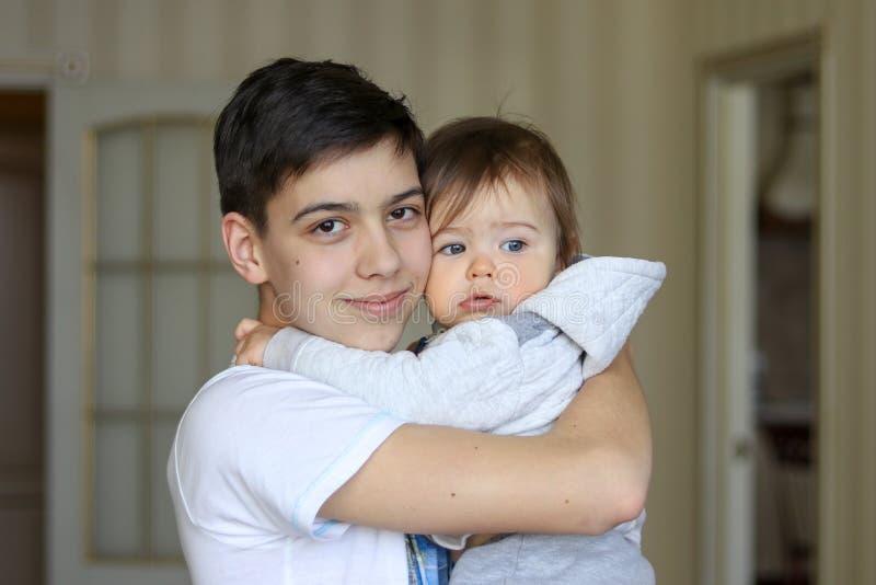 Garçon heureux d'adolescent et son petit frère mignon s'étreignant photographie stock libre de droits