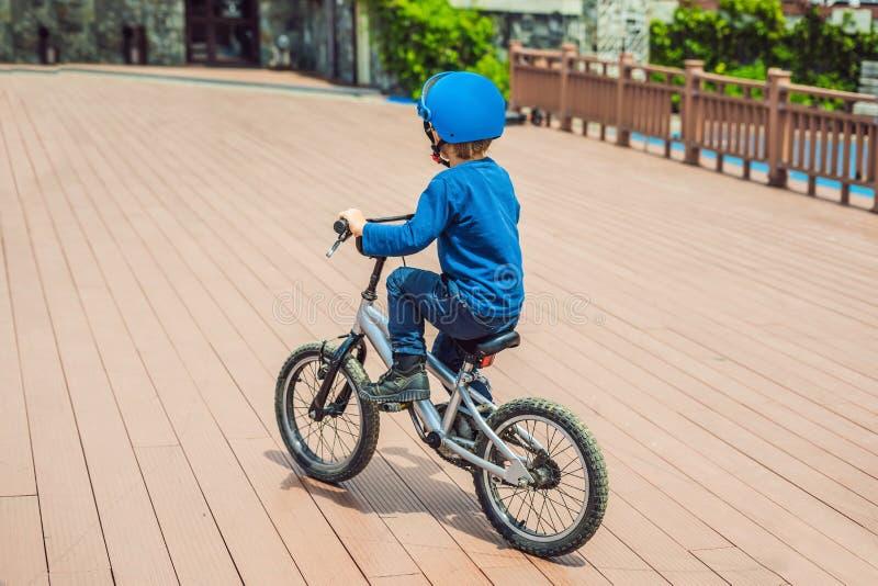 Garçon heureux d'enfant ayant l'amusement près du club de yacht avec une bicyclette le beau jour Casque de port de vélo d'enfant  image libre de droits