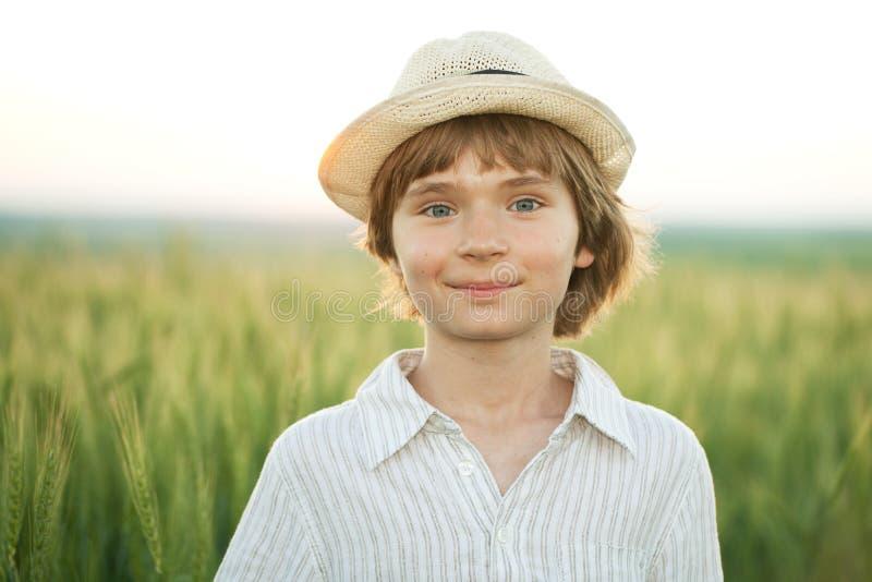 Garçon heureux dans le chapeau parmi la zone de blé photographie stock libre de droits