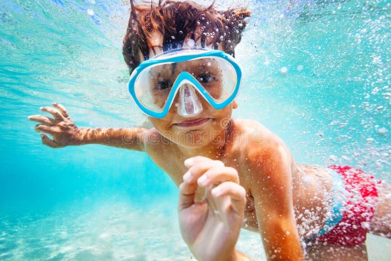 Garçon heureux dans le masque de scaphandre nageant sous l'eau photo stock