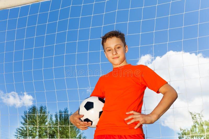 Garçon heureux dans le T-shirt orange avec le football photographie stock