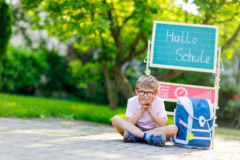 Garçon heureux de petit enfant avec des verres se reposant par le bureau et le sac à dos ou la sacoche Écolier avec le sac d'écol photo libre de droits