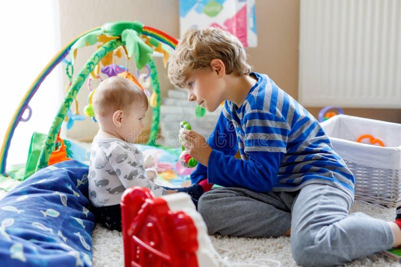 Garçon heureux de petit enfant avec le bébé nouveau-né, soeur mignonne siblings Frère et bébé jouant ensemble Un enfant plus âgé images libres de droits