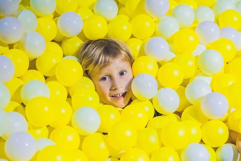 Garçon heureux de petit enfant jouant à la vue élevée de terrain de jeu en plastique coloré de boules Enfant adorable ayant l'amu image libre de droits