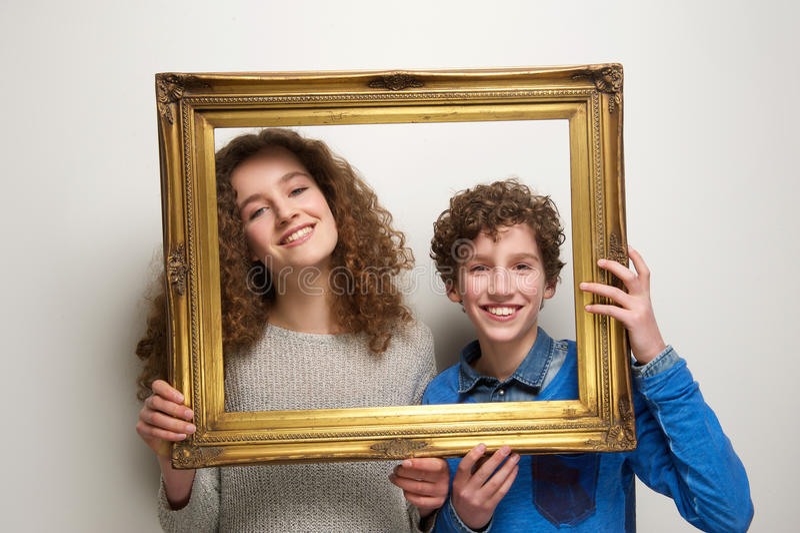Garçon heureux et fille tenant le cadre de tableau images libres de droits