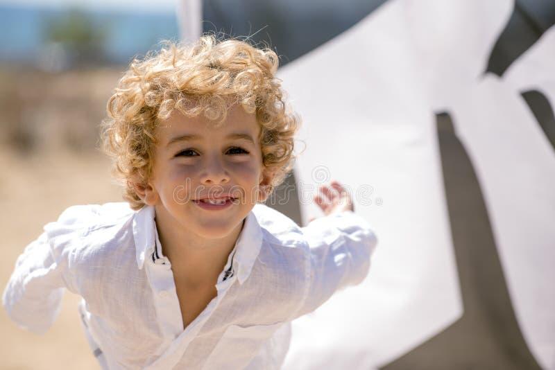 Garçon heureux jouant sur la plage photo libre de droits
