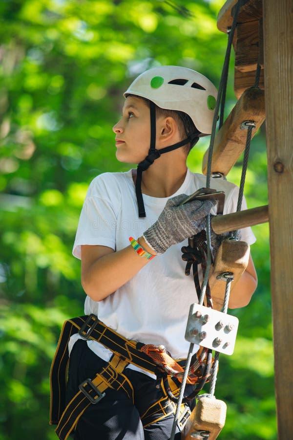 Garçon heureux, mignon, jeune dans le T-shirt blanc et casque ayant l'amusement et jouant au parc d'aventure, tenant des cordes e image stock