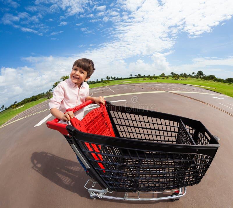 Garçon heureux montant le caddie vide de supermarché image libre de droits