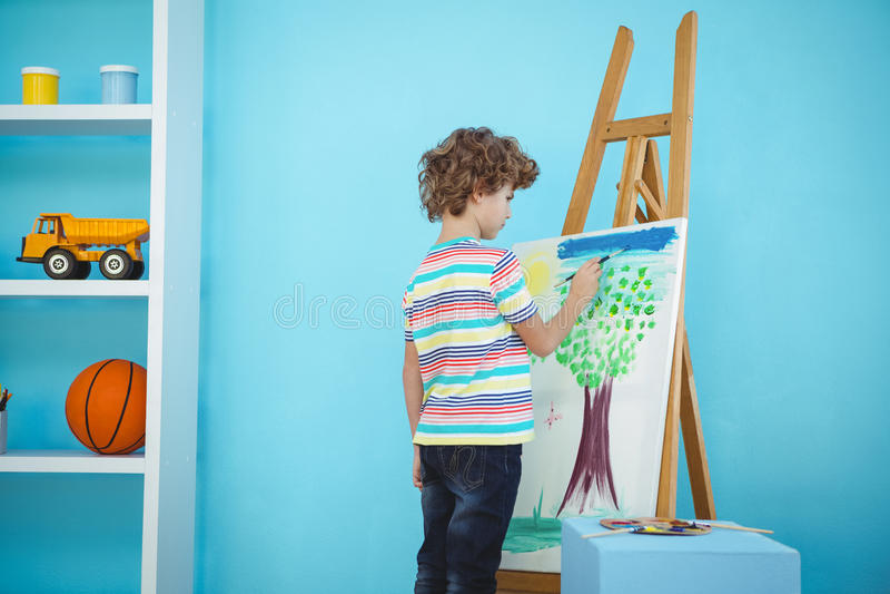 Garçon heureux peignant le sien photo photo stock