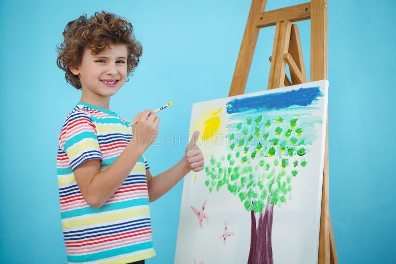Garçon heureux peignant le sien photo photographie stock