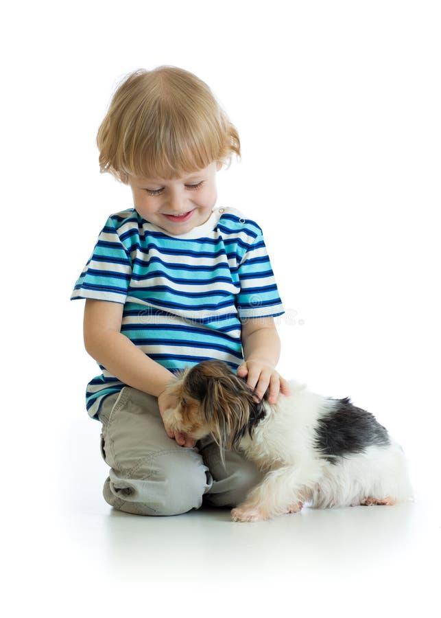 Garçon heureux s'asseyant avec le chiot de chien d'isolement sur le fond blanc photos stock