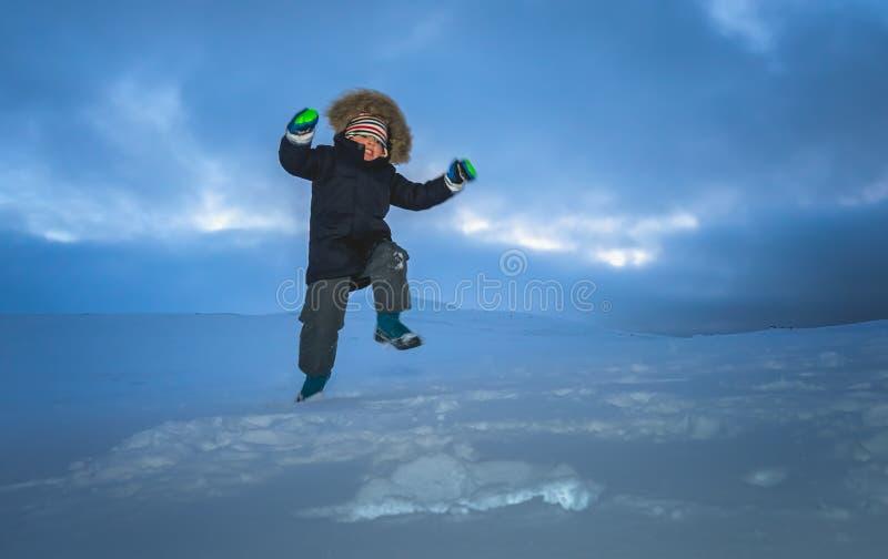 Garçon heureux sautant dans la neige photo libre de droits