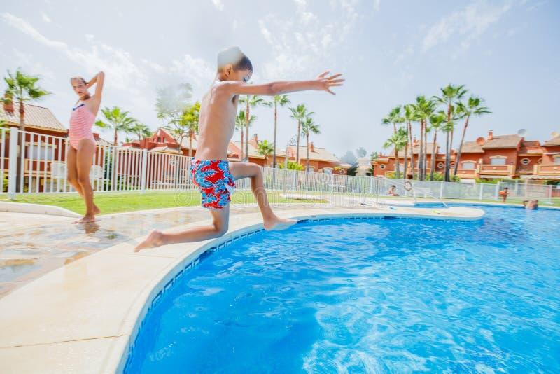Garçon heureux sautant dans la piscine photo libre de droits