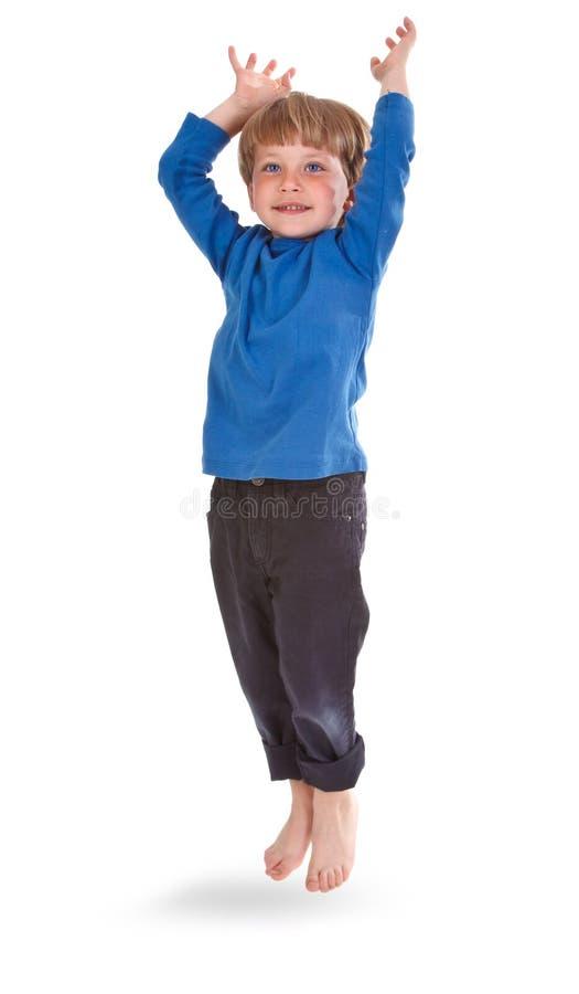 Garçon heureux sautant par-dessus le fond blanc images libres de droits