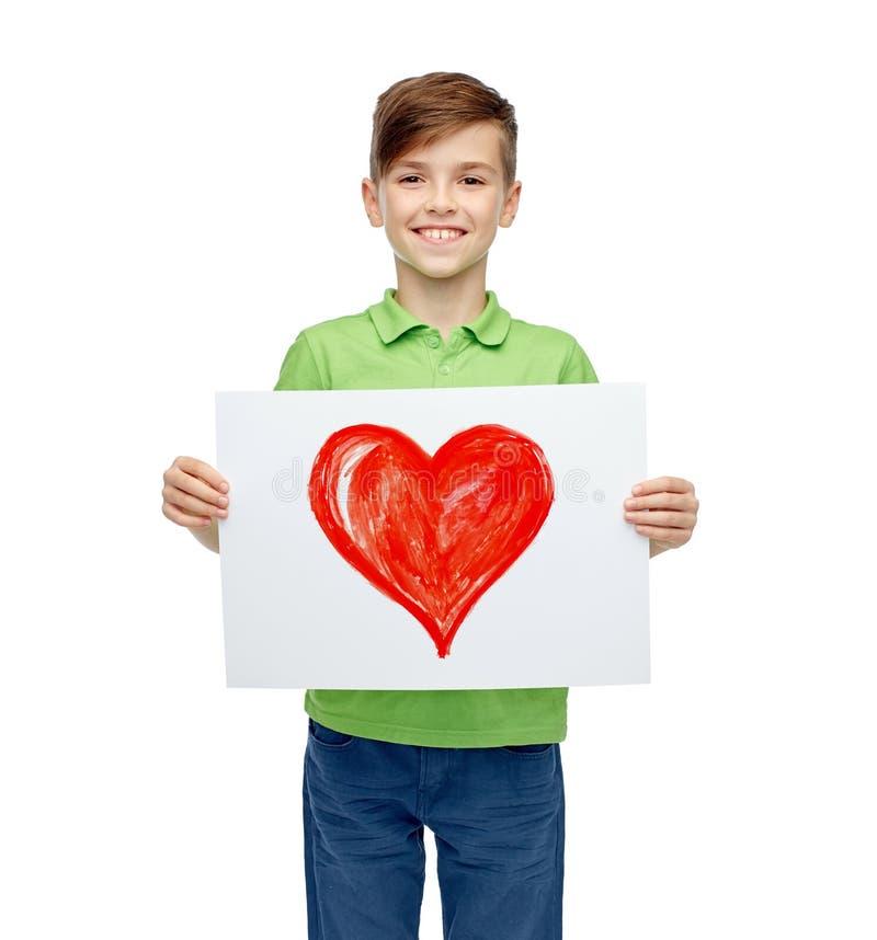 Garçon heureux tenant le dessin ou la photo du coeur rouge photo libre de droits