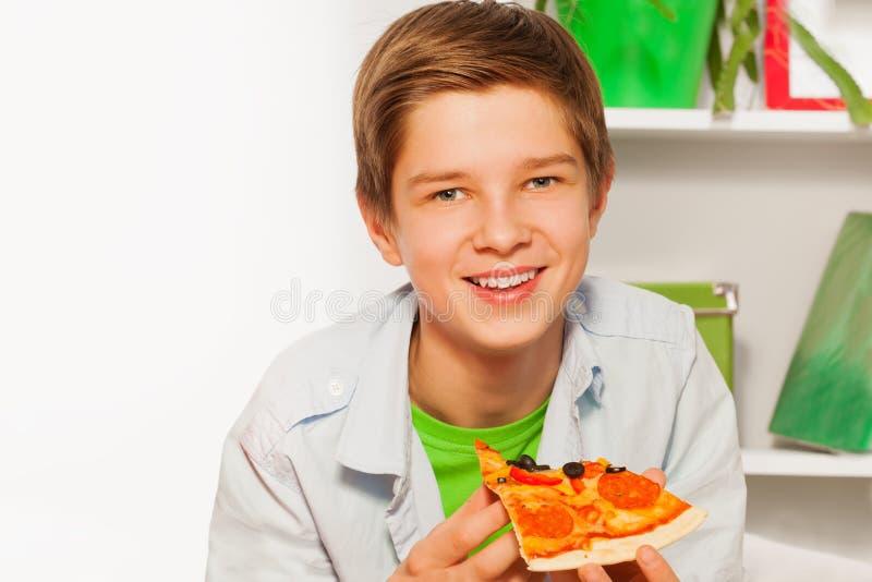 Garçon heureux tenant le morceau de pizza et mangeant à la maison image stock