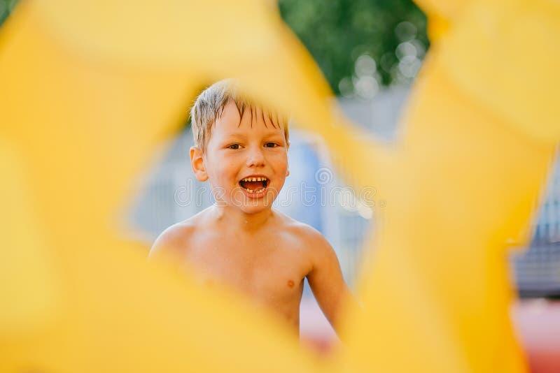 Garçon humide d'amusement sur la plage en été par le trou, cadre, piaulant photographie stock