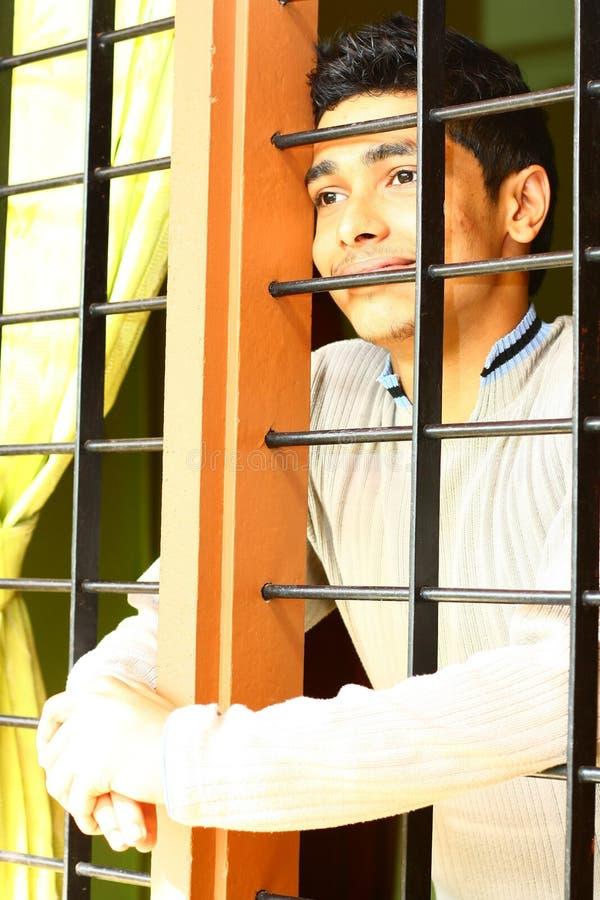 Garçon indien rêveur regardant à l'extérieur par l'hublot photos libres de droits