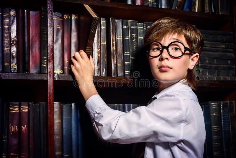 Garçon intelligent dans une bibliothèque photo libre de droits