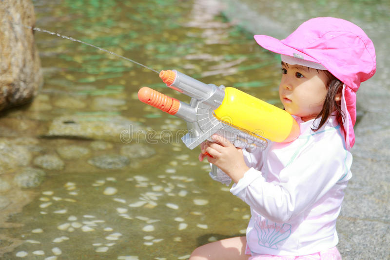 Garçon japonais jouant avec l'arme à feu d'eau photo stock