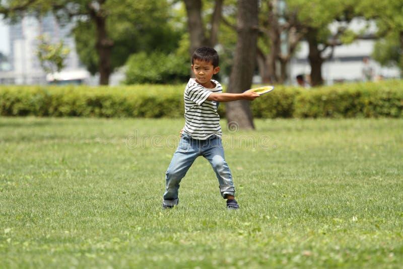 Garçon japonais jouant le disque de vol photo stock