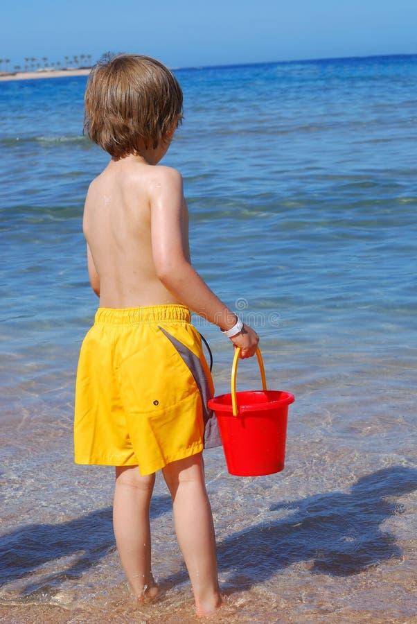 Garçon jouant à la plage photos stock