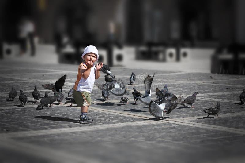 Garçon jouant au centre de la ville photos libres de droits