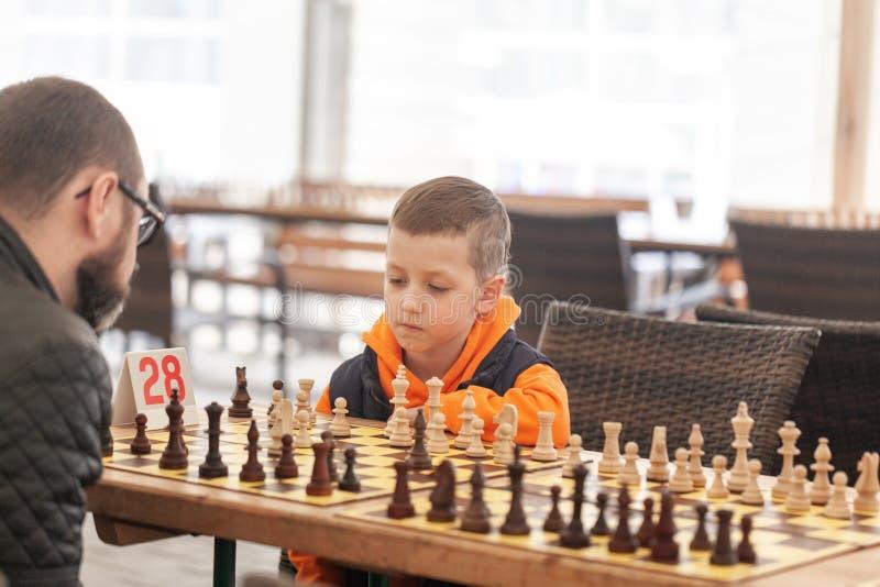 Garçon jouant aux échecs avec le père sur un tournoi d'échecs de famille à une école images stock