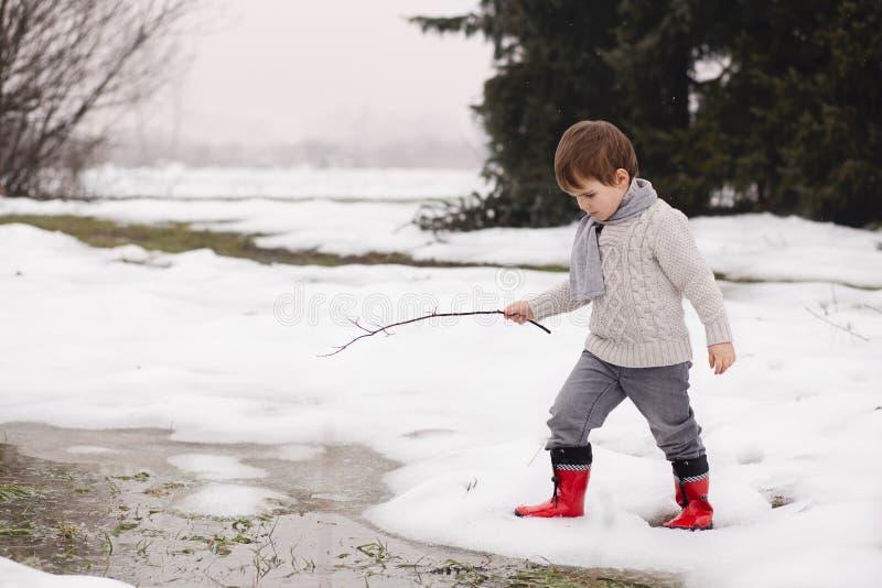 Garçon jouant avec de l'eau congelé en hiver photo stock