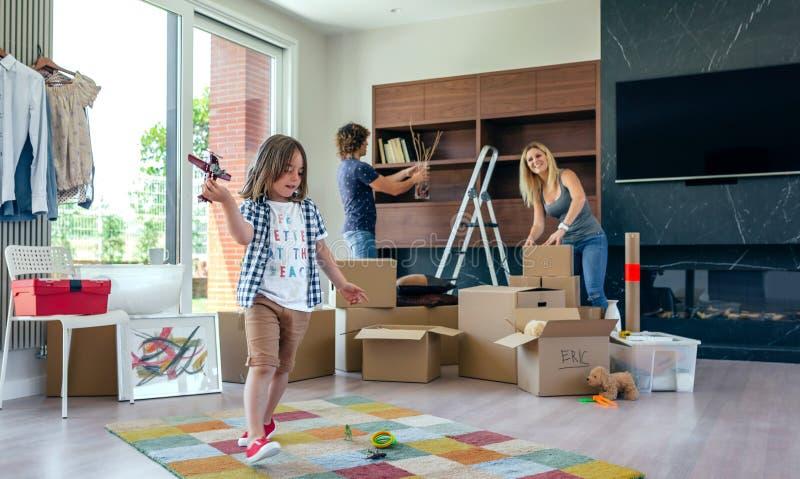 Garçon jouant avec l'avion de jouet tandis que les parents déballent images stock