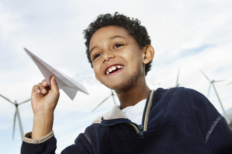 Garçon jouant avec l'avion de papier à la ferme de vent photos stock