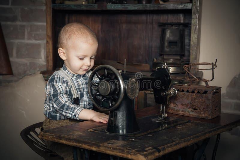 Garçon jouant avec la coudre-machine images libres de droits