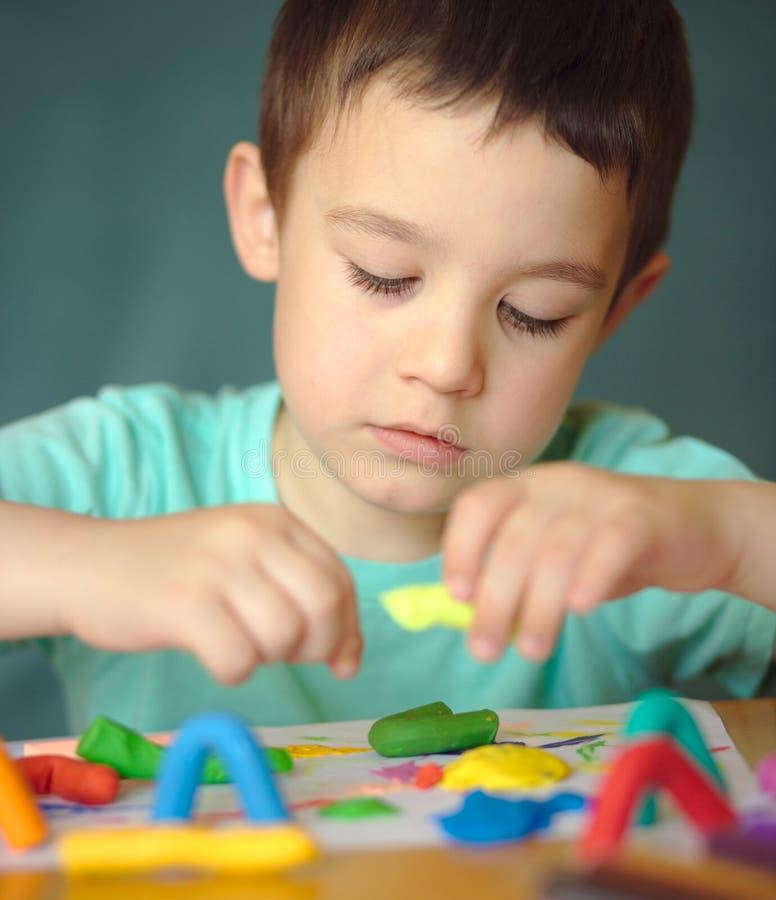 Garçon jouant avec la pâte de jeu de couleur photos stock