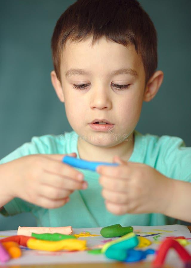 Garçon jouant avec la pâte de jeu de couleur photographie stock libre de droits