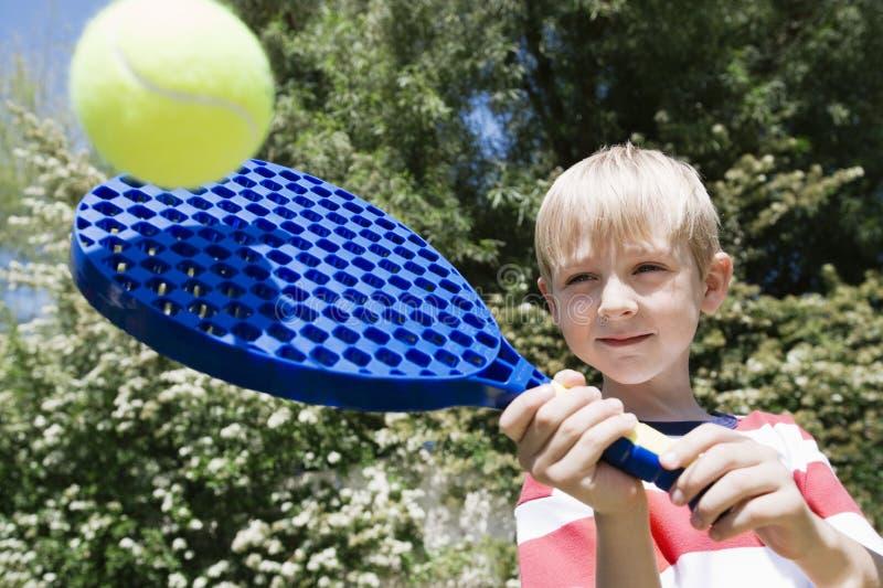 Garçon jouant avec la palette et la boule photo libre de droits