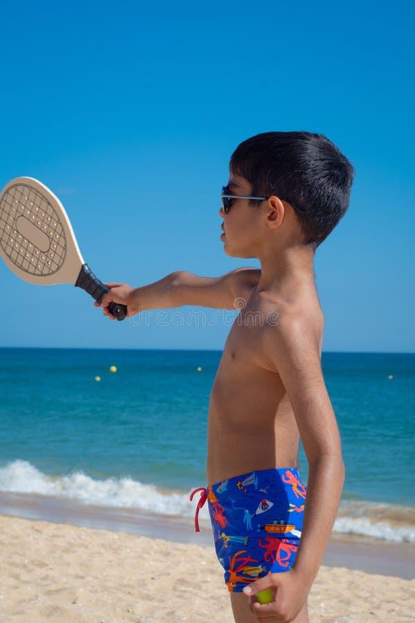 Garçon jouant avec la raquette à une plage des vacances photos libres de droits