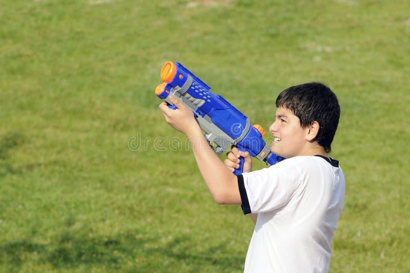 Garçon jouant avec le canon d'eau photos stock