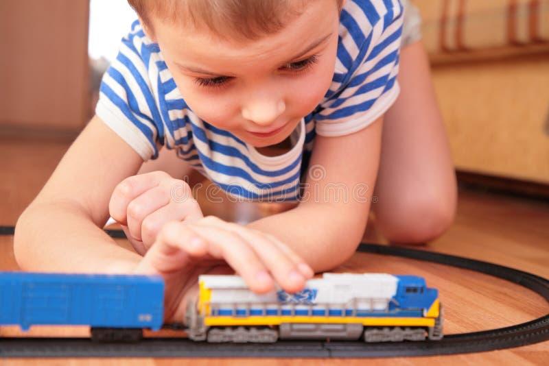 Garçon jouant avec le chemin de fer de jouet image libre de droits
