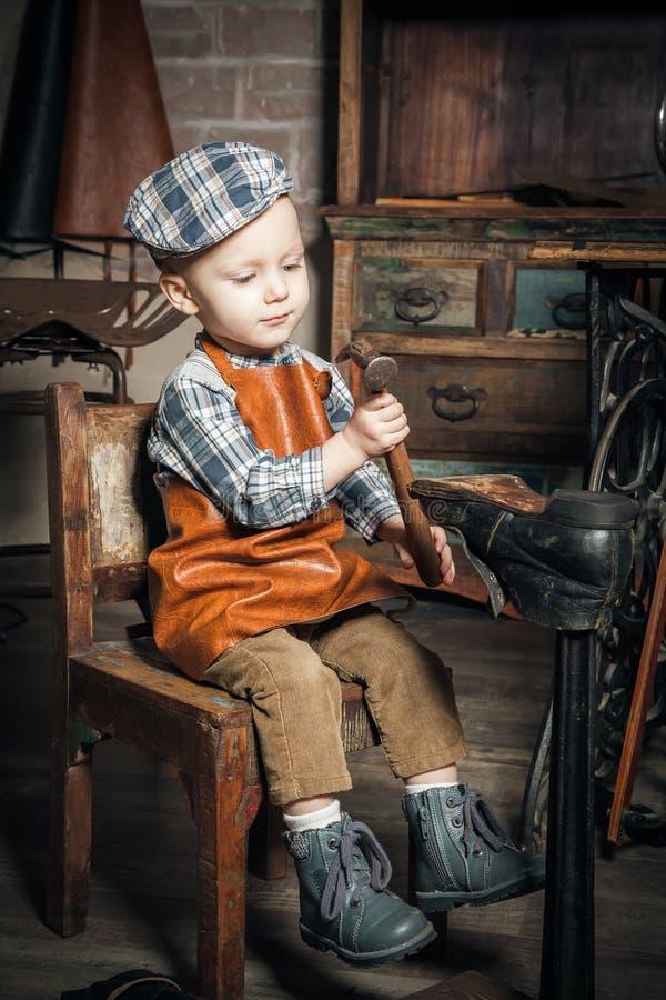 Garçon jouant avec le marteau et la chaussure photographie stock