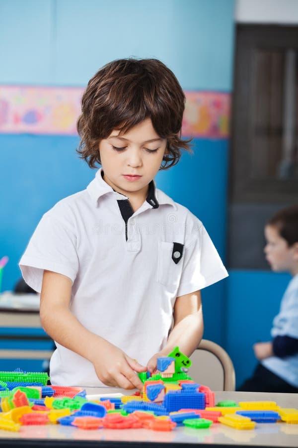 Garçon jouant avec les blocs colorés dans la salle de classe images stock