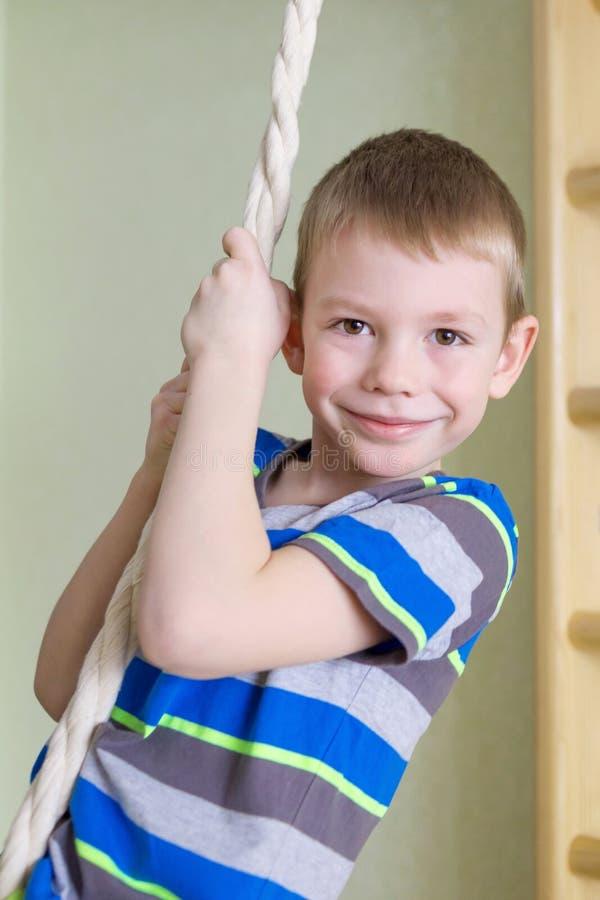 Garçon jouant des sports sur la corde dans la classe de gymnase photos stock