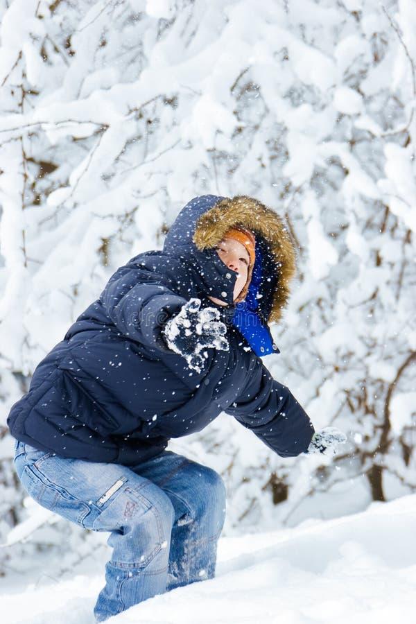 Garçon jouant en stationnement de l'hiver photographie stock