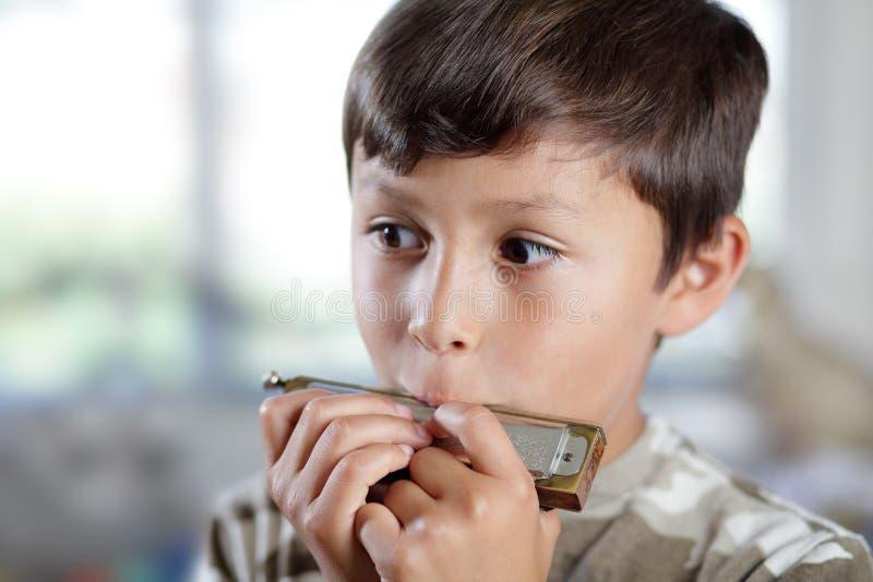 Garçon jouant l'harmonica photos libres de droits
