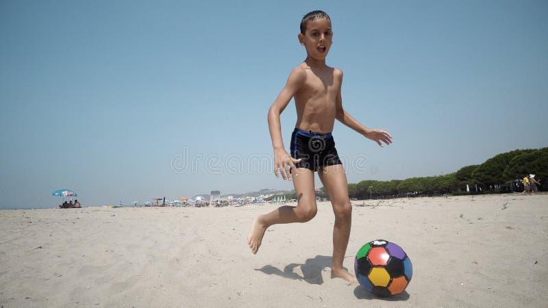 Garçon jouant le ballon de football sur la plage pendant des vacances d'été photo stock