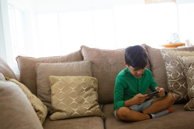 Garçon jouant le jeu au téléphone portable tout en se reposant sur le sofa à la maison image libre de droits