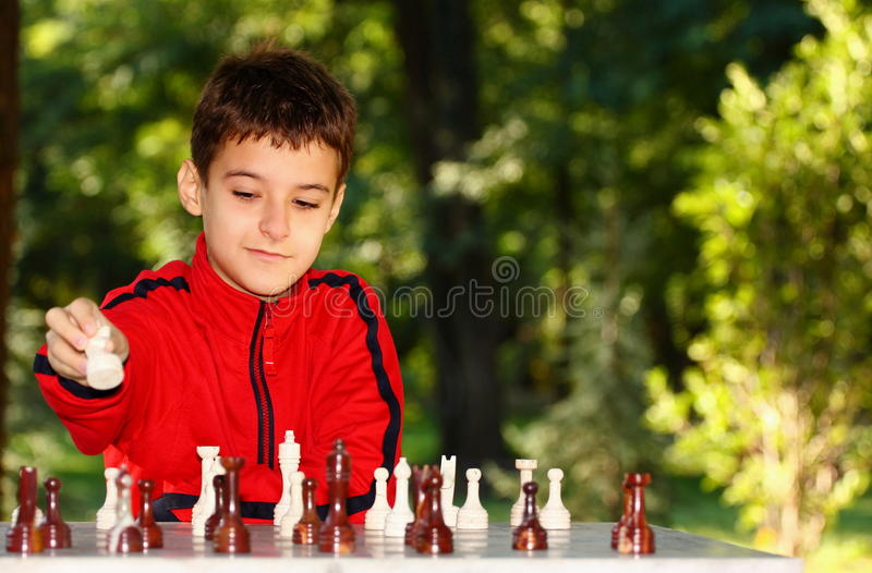 Garçon jouant le jeu d'échecs photo stock