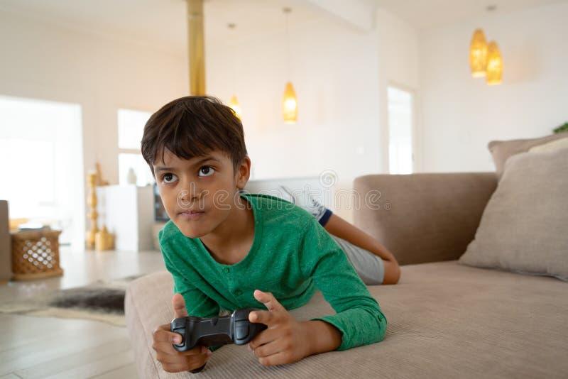 Garçon jouant le jeu vidéo sur le sofa dans le salon à la maison confortable images libres de droits