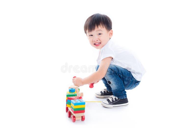 Garçon jouant le jouet sur le plancher au-dessus du fond blanc images stock